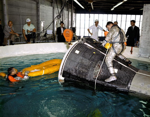 Astronauts John Young and Gus Grissom are pictured during water egress training in a large indoor pool at Ellington Air Force Base, Texas, in this image from 1965